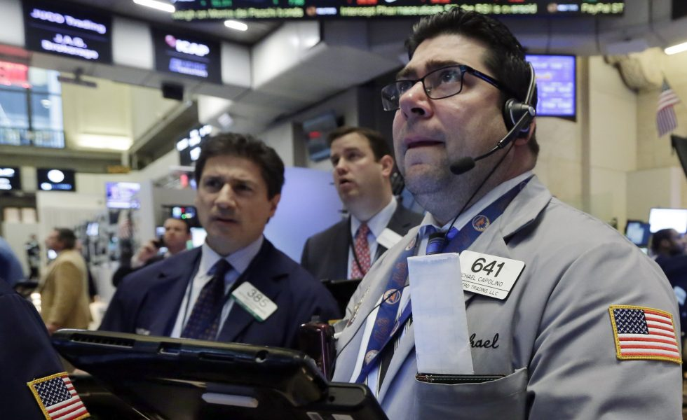 Trader Michael Capolino (right) watches prices on the floor of the New York Stock Exchange Wednesday. Stocks endured another bloodbath, and oil fell below $27 a barrel.